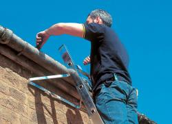 cleaning gutters on an extension ladder