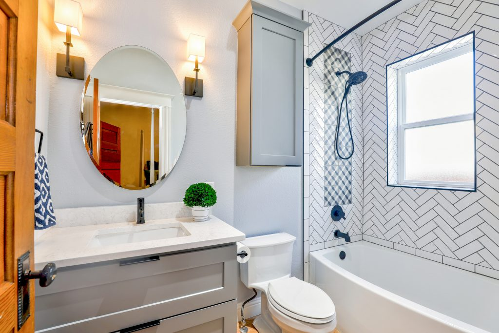 bathroom photo with a grey cabinet, a round mirror and zig zag tile in the shower