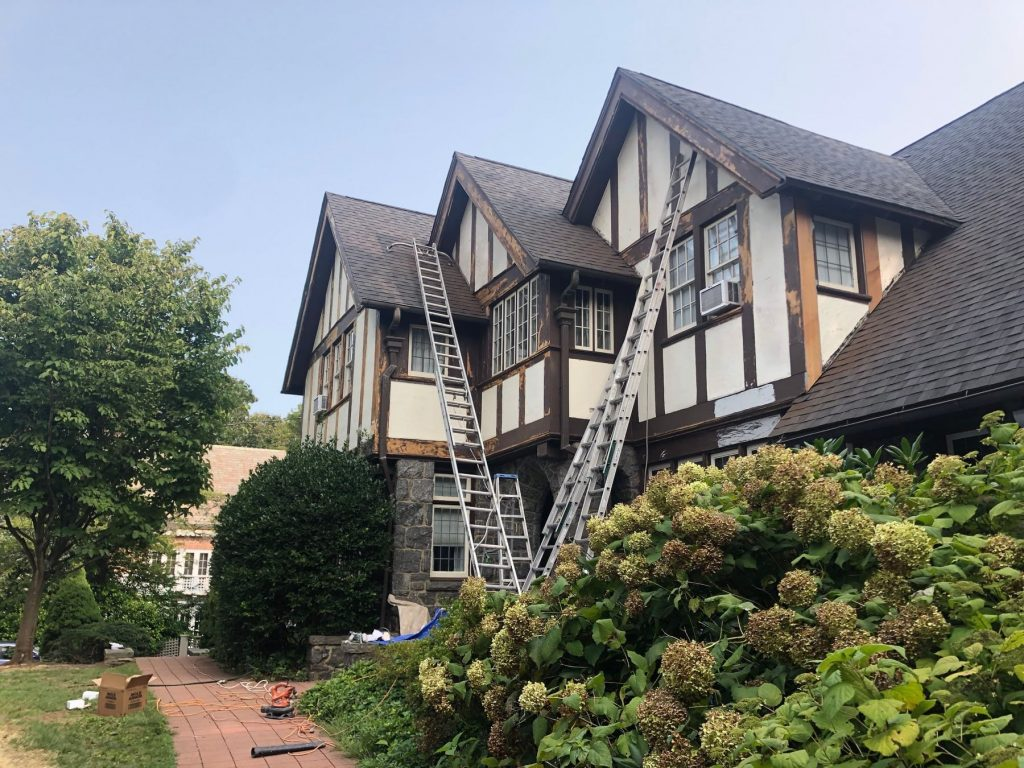 three eave home that has brown trim and tan siding. The brown trim is partially stripped and ready for repairs. there are ladders leaning against the house