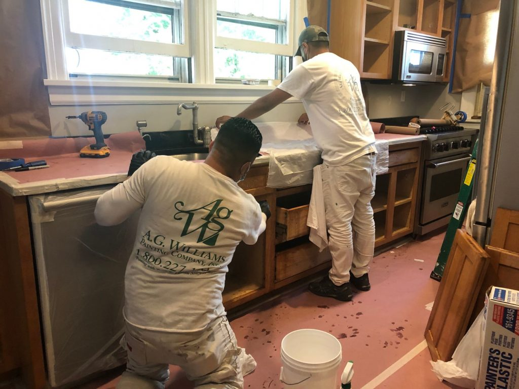 men working in kitchen repainting wood cabinets