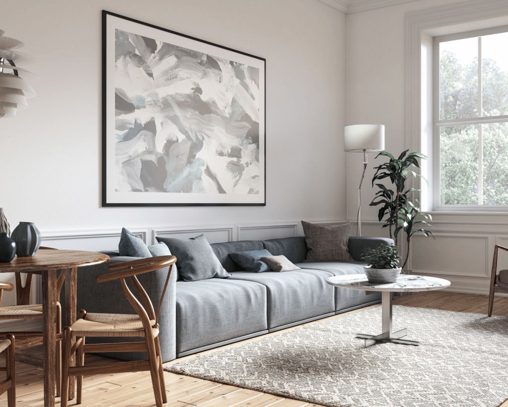 room with light grey walls and a dark grey sofa with blue accent pillows