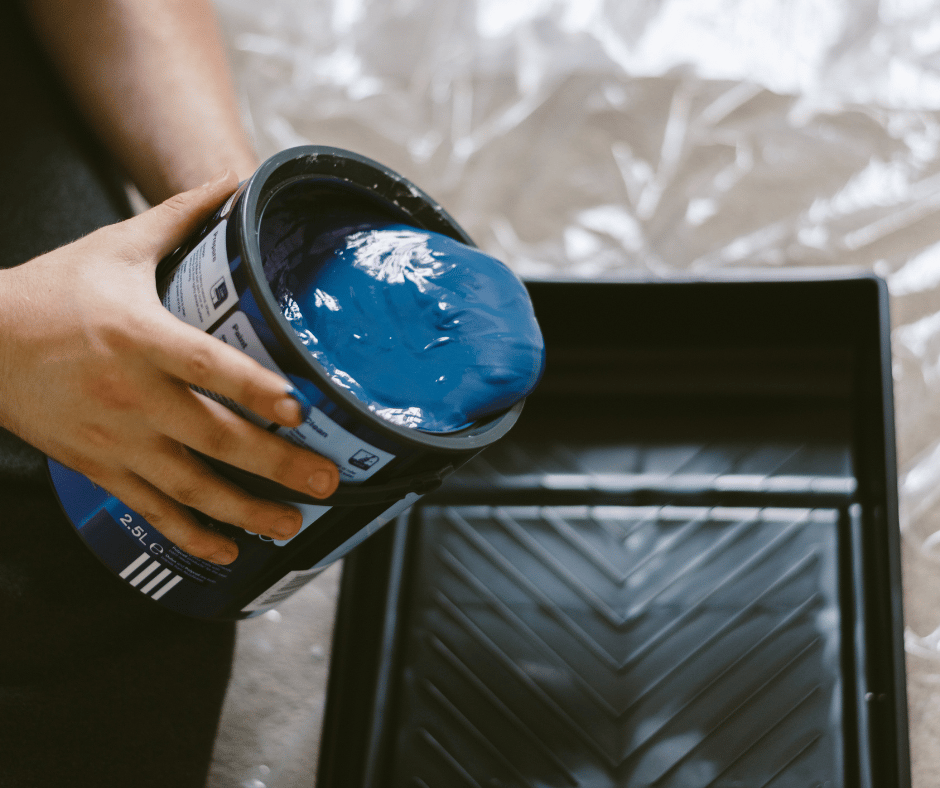 blue paint being poured into black paint tray